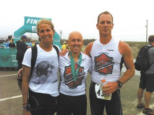 Joe Caruso, center, is flanked by teammates Kathy Lewis and Mitch Turner on Saturday after the trio completed the Amica 19.7 Newport sprint triathlon. Caruso, who was first diagnosed with cancer in 2009, completed the 16.1-mile bike portion.